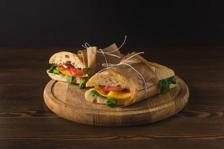 Deux délicieux panini cuits avec des légumes sur une planche de bois Banque d'images - 98683184