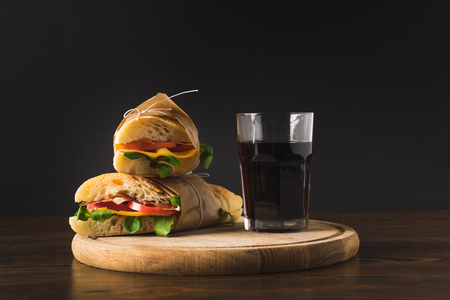two panini on each other and glass of cola on wooden board