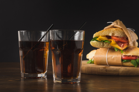 Deux verres de cola sur table et panini sur planche de bois Banque d'images - 98683194