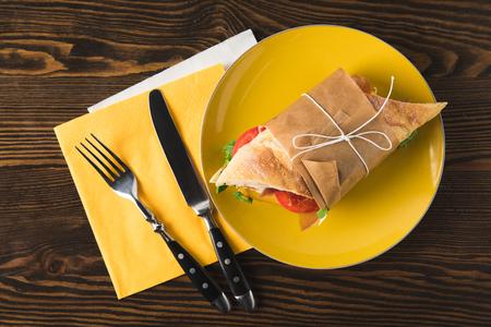 Vue de dessus du panini sur plaque jaune avec fourchette et couteau Banque d'images - 98683199