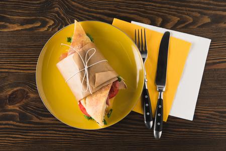 Vue de dessus du panini sur une plaque jaune avec une fourchette et un couteau sur des serviettes Banque d'images - 98683207