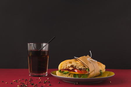 panini with vegetables and glass of cola on table