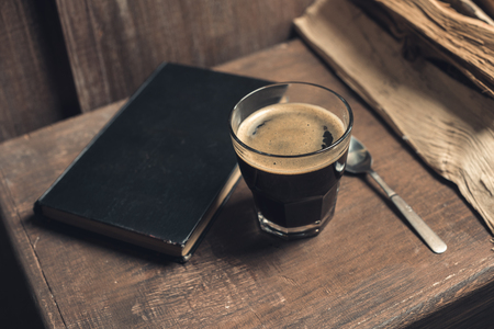 Glass of coffee drink, old book and spoon on rustic wooden table near pile of firewood 写真素材