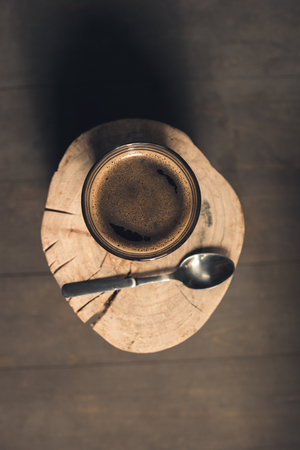 top view of glass of coffee drink and spoon on wood log  写真素材