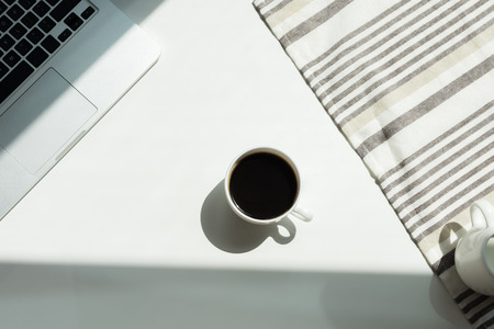White working desk with laptop computer and cup of black coffee and tablecloth