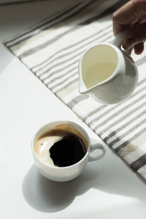 Person pouring milk from jug into cup of black coffee on white table with tablecloth Stock Photo