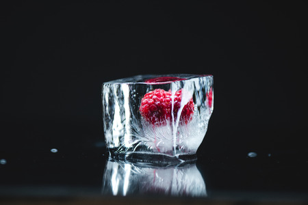 close-up view of ripe juicy raspberry frozen in ice cube on black  写真素材