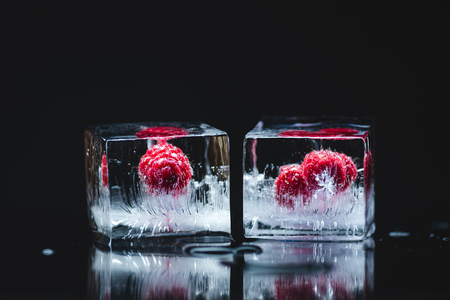 close-up view of ripe juicy raspberries frozen in ice cubes on black  写真素材