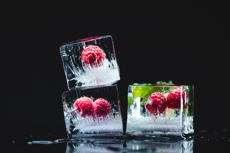 close-up view of ripe juicy raspberries with green leaves frozen in ice cubes on black  写真素材