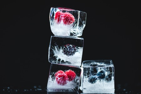 close-up view of ripe frozen berries in ice cubes on black