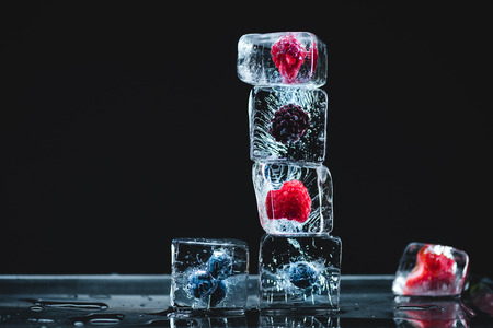 ripe juicy frozen fruits in ice cubes melting on black