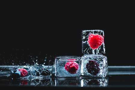 ripe frozen berries in transparent ice crystals and water drops on black