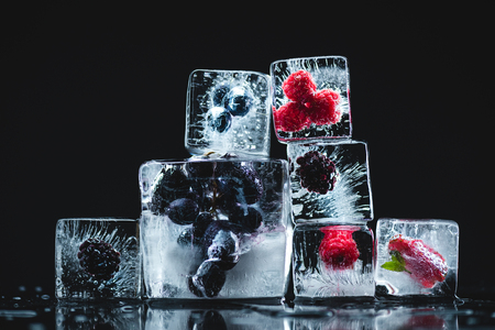 close-up view of ripe juicy frozen berries in ice cubes on black   写真素材