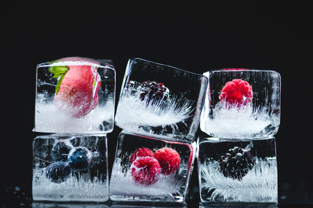 close-up view of ripe juicy berries frozen in ice cubes on black