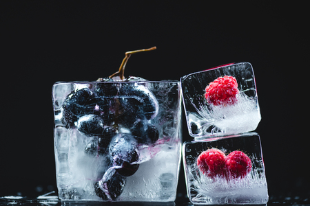 close-up view of frozen juicy grapes and ripe raspberries in ice crystals on black