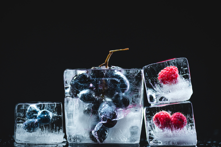 close-up view of frozen blueberries, raspberries and grapes in ice cubes on black