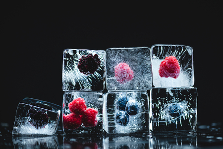close-up view of ripe gourmet frozen berries in ice crystals on black