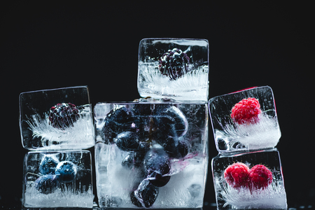 close-up view of ripe juicy berries frozen  in ice crystals on black