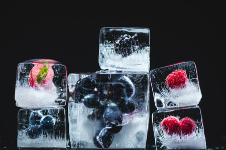 close-up view of gourmet frozen fruits in ice cubes on black