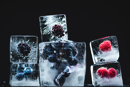 close-up view of juicy ripe fruits frozen in ice cubes on black