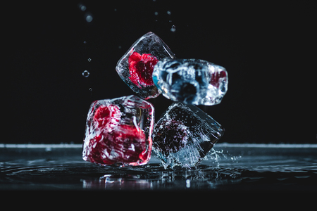 close-up view of ripe frozen berries in ice cubes falling on black 写真素材
