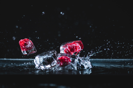 fallen ripe frozen fruits in transparent ice cubes and splashing water on black