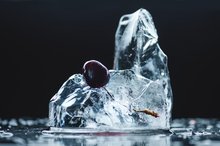 close-up view of ripe juicy cherry in melting ice crystal on black 写真素材
