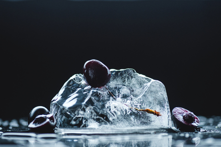 close-up view of ripe juicy cherries with melting ice crystal on black 写真素材