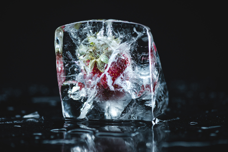 close-up view of ripe strawberry frozen in ice cube on black 写真素材