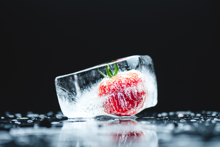 close-up view of ripe cherry tomato frozen in ice cube on black