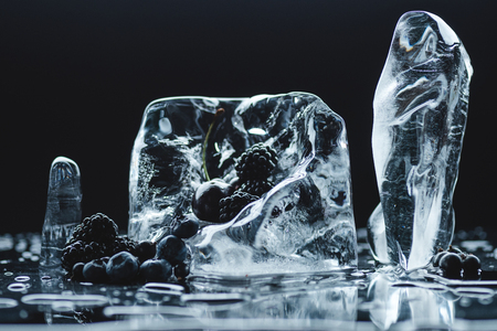 close-up view of ripe blueberries and blackberries with transparent melting ice crystals on black