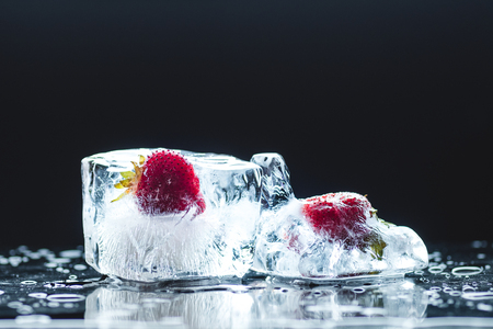 close-up view of ripe frozen strawberries in melting ice cubes on black