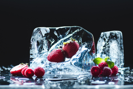 ripe juicy strawberries and raspberries with transparent melting ice crystals on black