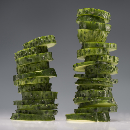 two stacks of sliced fresh cucumbers isolated on grey