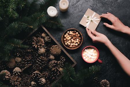 flat lay with female hands holding gift card, pine cones in wooden box, cup of cacao with marshmallow on dark tabletop Banco de Imagens
