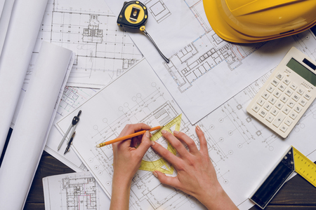 partial view of architect working on blueprints at workplace with architect equipment Reklamní fotografie