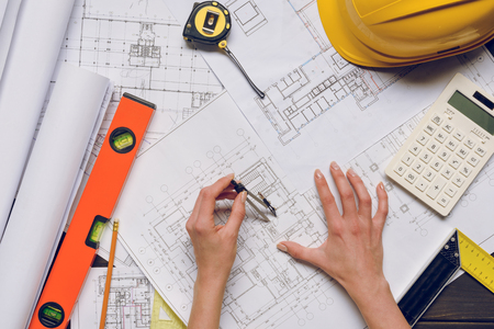 partial view of architect working on blueprints at workplace with architect equipment