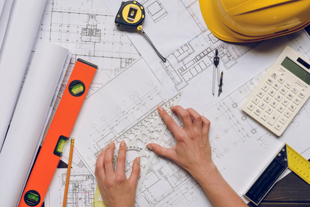 partial view of architect working on blueprints at workplace with calculator