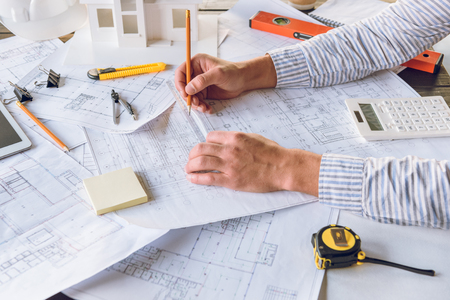 partial view of architect working with blueprints on new building design