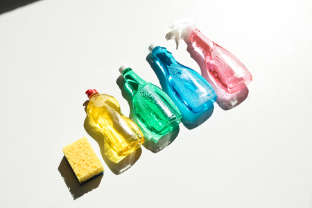 close-up view of plastic bottles with colorful cleaning products and sponge on white