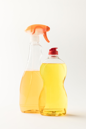 close-up view of plastic bottles with yellow cleaning fluids isolated on white