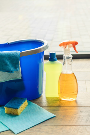 close-up view of plastic bottles with cleaning fluids, sponge, rags and bucket on floor