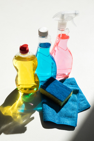 close-up view of plastic bottles with colorful cleaning products, sponge and rag on white 写真素材