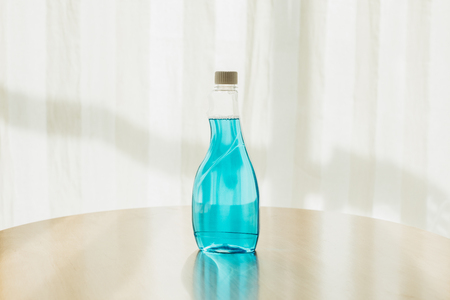 close-up view of plastic bottle of blue cleaning fluid on tabletop