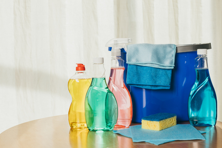 plastic bottles with cleaning fluids, sponge, rags and bucket indoors