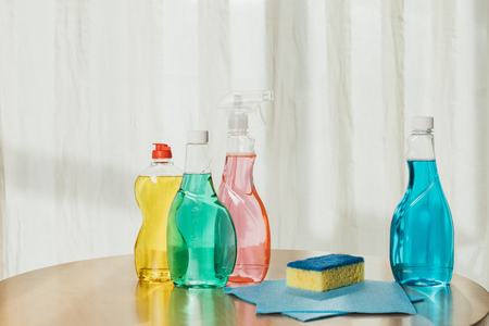 plastic bottles with colorful cleaning products, sponge and rags on tabletop