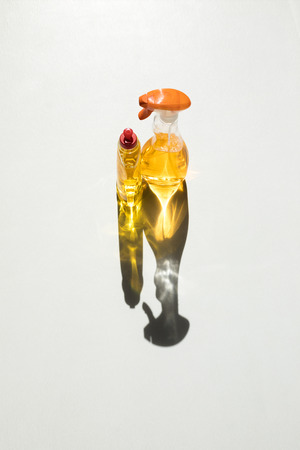 high angle view of plastic bottles with yellow cleaning fluids on white