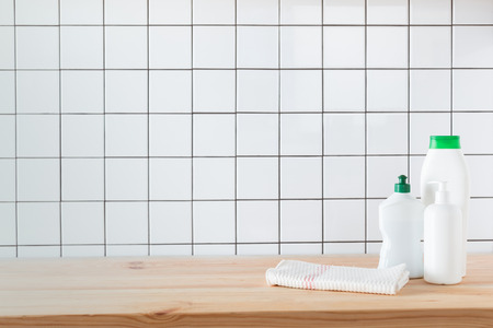 plastic bottles with cleaning products and towel on tabletop