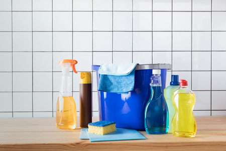 close-up view of various cleaning supplies on wooden tabletop
