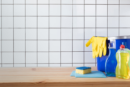 various cleaning products, sponge, rags and bucket with protective gloves on tabletop